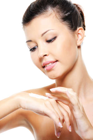 Photo pour Beautiful pretty young girl caring of her hands treatment cosmetic cream - image libre de droit
