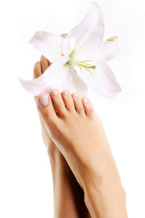 Beautiful healthy female feet with lily flowers on a white background