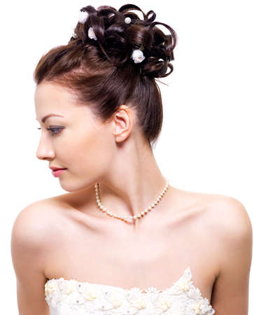 Profile portrait of a beautiful bride with wedding hairstyle - on white background