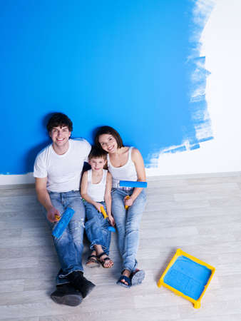 Photo pour Happy family having a rest after painting the wall - high angle - image libre de droit