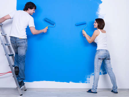 Photo pour Young couple in casuals ñoloring the wall in blue - rear view - image libre de droit