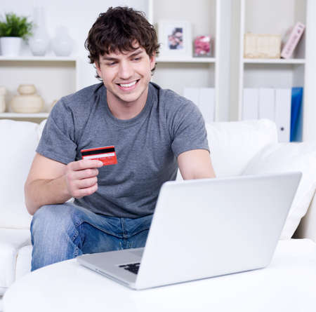 Handsome man holding credit card and using laptop for online shopping - indoors
