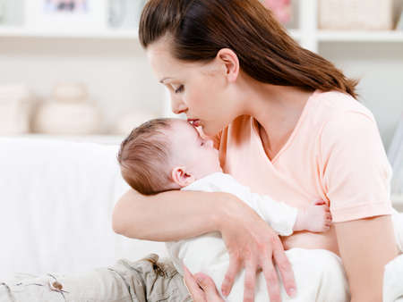 Photo pour Young mother kissng her small sleeping newborn baby - indoors - image libre de droit