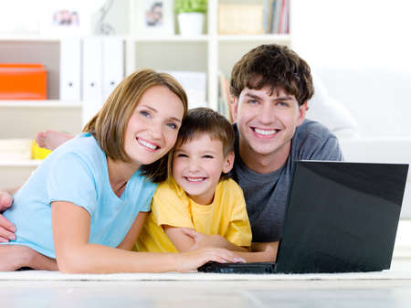 Photo pour Beautiful happy family with little son relaxing at home with laptop - indoors - image libre de droit