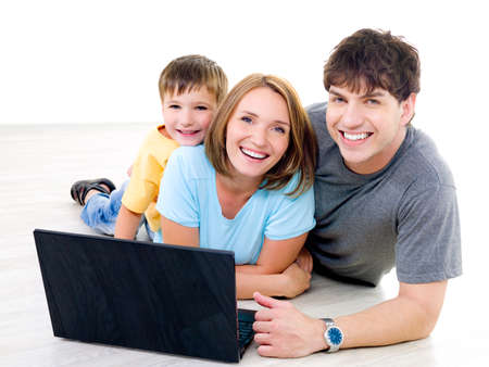 Photo pour Three happy laughing people with little boy on the floor with laptop - indoors - image libre de droit