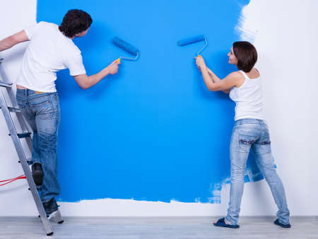 Photo pour Coloring the wall in blue by young couple in casuals - horizontal - image libre de droit