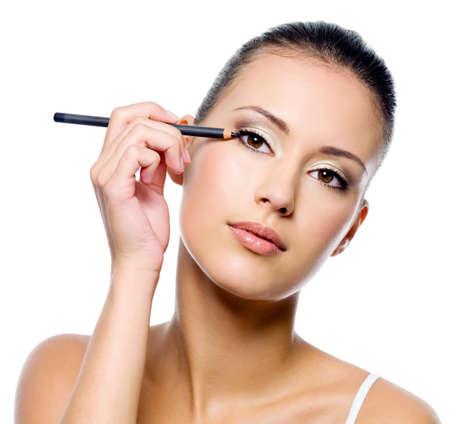 Young beautiful woman applying eyeliner on eyelid with pencil - isolated