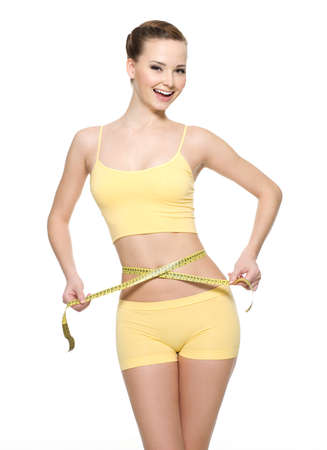 Pretty smiling woman measuring waist with  measurement type isolated on white