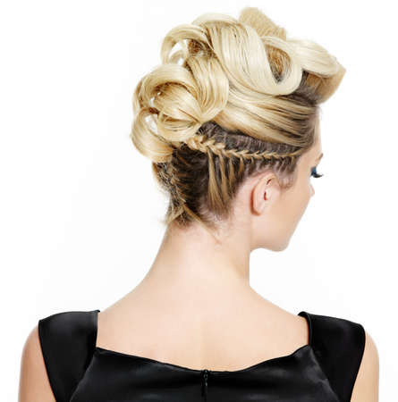Blond female with creative curly  hairstyle, rear view on white background