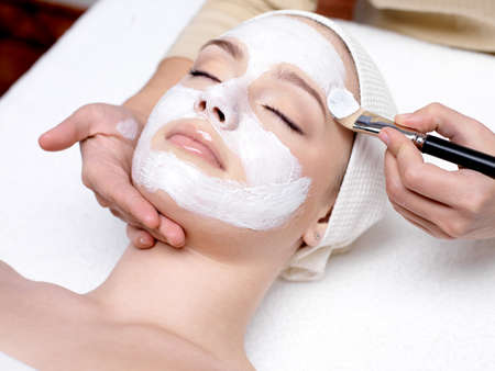 Beautiful young woman receiving facial mask at beauty salon - indoorsの写真素材