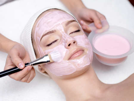 Young beautiful girl receiving pink facial mask in spa beauty salon - indoorsの写真素材