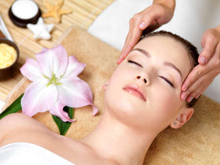 Beautiful young woman having spa massage of the head  in beauty salon - indoorsの写真素材