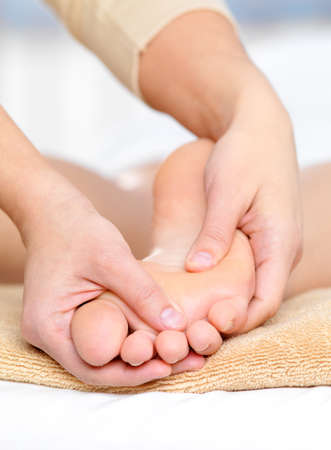 Healthy massage for caucasian foot in spa beauty salon - close-up