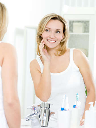 Beautiful smiling young woman with fresh skin of face posing in bathroom