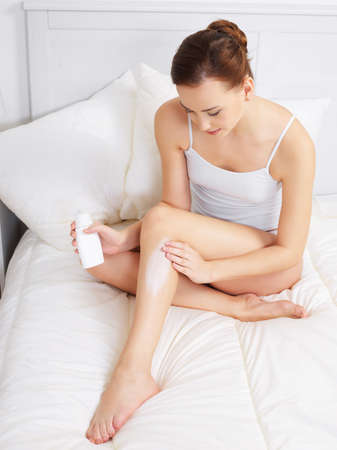 Photo pour Pretty young adult woman applying cream for skin on legs - indoors - image libre de droit