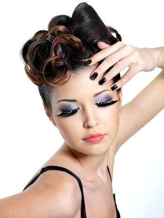 Glamour woman with  fashion eye make-up   and black nails near the face