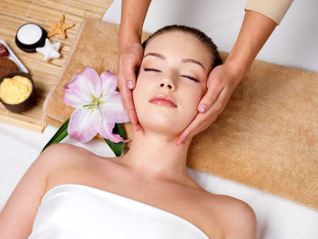 Relaxing beautiful woman having a massage for her skin on a face in beauty salon - horizontalの写真素材