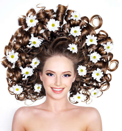 Smiling young woman with flowers in long hair - white background