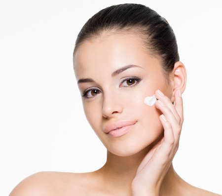 Portrait of beautiful woman applying cream on face - isolated on white