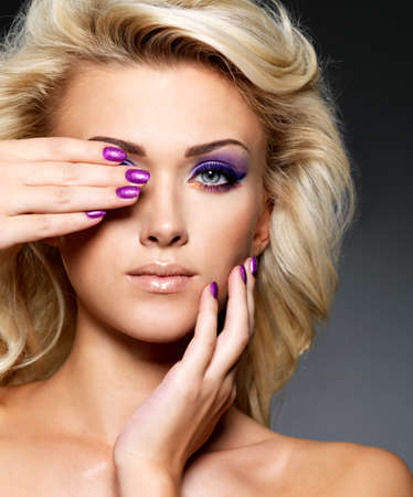Beautiful blond woman with beauty purple manicure and makeup of eyes  Fashion model with curly hairstyle