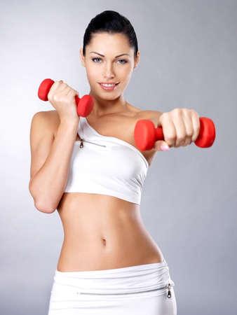 Foto de Photo of a healthy training young woman with dumbbells.  Healthy lifestyle concept. - Imagen libre de derechos