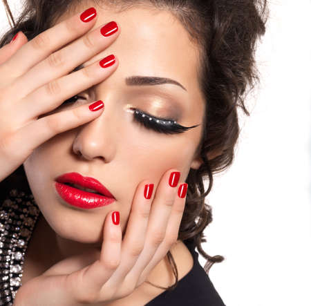 Beautiful fashion model with red nails, lips and creative eye makeup  - isolated on white background