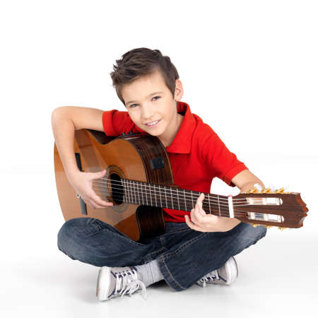 Handsome happy  boy is playing on acoustic guitar - isolated on white background