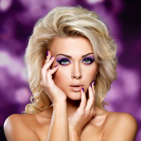 Photo pour Beautiful blond woman with  purple makeup of eyes. Fashion model with curly hairstyle. Blinking Background. Bokeh - image libre de droit