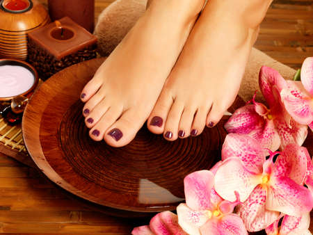 Photo pour Closeup photo of a female feet at spa salon on pedicure procedure. Legs care concept - image libre de droit