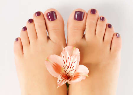 Closeup photo of a female feet with beautiful pedicure after spa procedure on white background