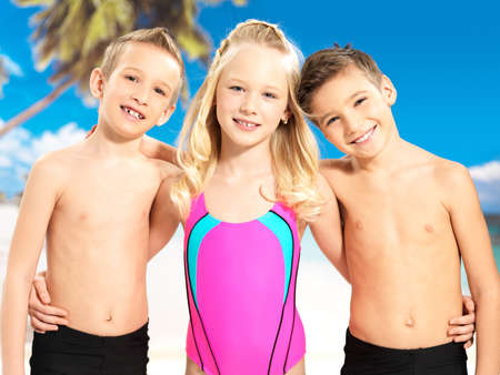 Portrait of the happy children enjoying at beach.  Schoolchild kids standing together in bright color swimwear.