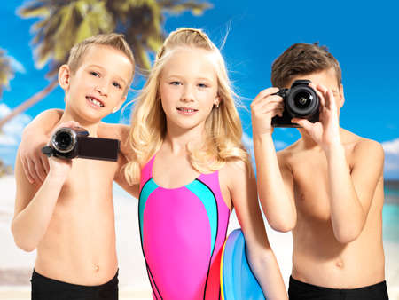 Portrait of the happy children enjoying at beach.  Schoolchild kids standing with photo and video camera in hands.