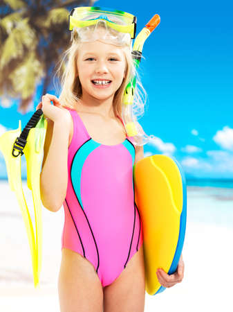 Portrait of the happy girl enjoying at beach.  Schoolchild girl stands  in bright color swimwear with swimming mask on head .