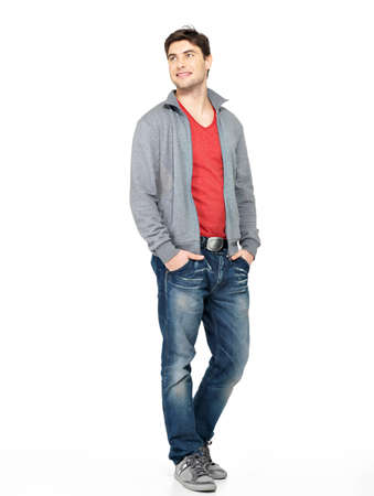 Photo pour Full portrait of smiling happy handsome man in grey jacket, blue jeans. Beautiful guy standing  isolated on white background loking away - image libre de droit