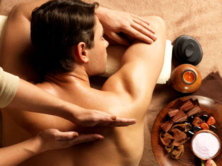 Masseur doing massage on man body in the spa salon. Beauty treatment concept.の写真素材