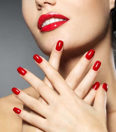 Young woman with fashion red nails and sensual lips - Model posing in studio