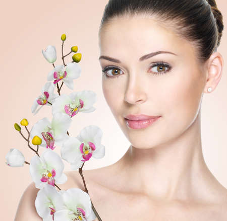 Adult woman with beautiful face and white flowers. Skin care concept.の写真素材