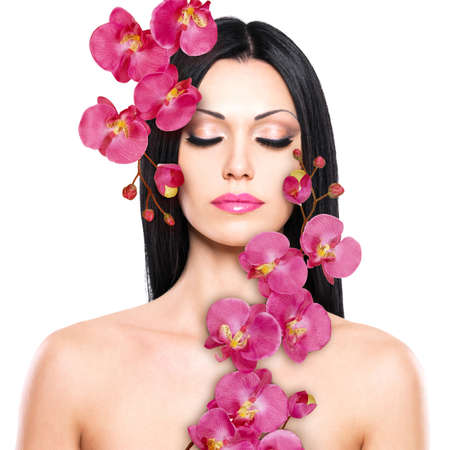 Young woman with beautiful face and fresh flowers. Skin care concept.の写真素材
