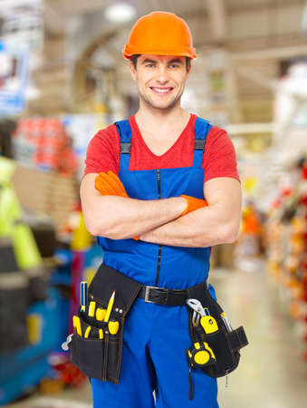 Portrait of smiling handyman stands at store