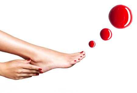 Beautiful female feet with red pedicure and drops of nail polish  over white backgroundの写真素材