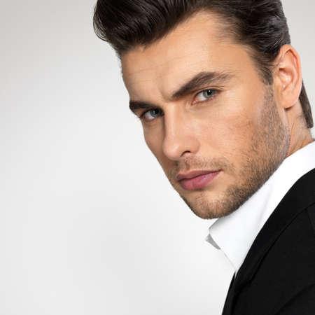 Photo pour Fashion young businessman black suit casual  poses at studio - image libre de droit