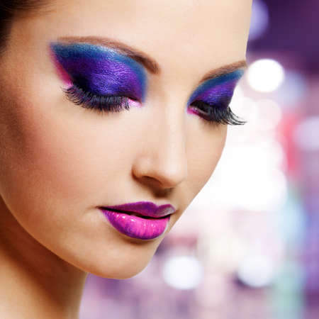 Beautiful female face with bright purple fashion makeup