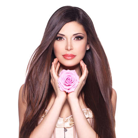 Photo pour Portrait of a beautiful white pretty woman with long straight hair and pink rose at face. - image libre de droit