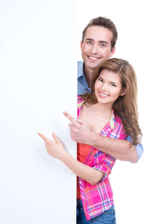 Portrait of beautiful happy couple showing at banner isolated on white background.