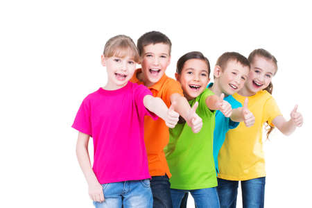 Foto de Group of happy kids with thumb up sign in colorful t-shirts standing together -  isolated on white. - Imagen libre de derechos
