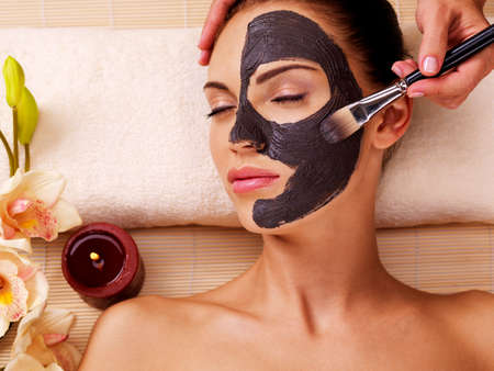 Photo pour Cosmetologist smears cosmetic mask on the face of the woman in the sap salon - image libre de droit