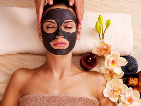 Photo pour Cosmetologist doing massage on the woman's face  in sap salon. Female with scrub cosmetic mask on face.  - image libre de droit