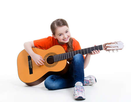 Photo pour Cute girl plays on the acoustic guitar with bright emotions -  isolated on white background. - image libre de droit