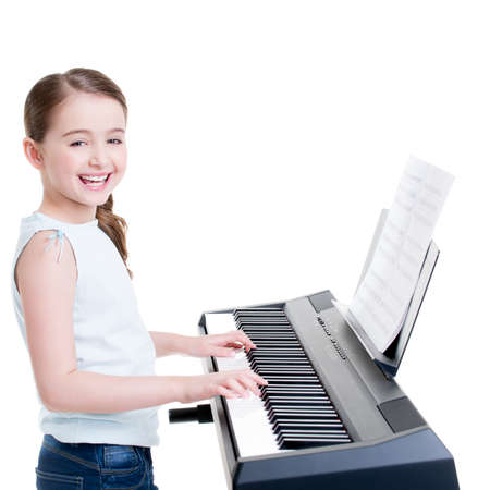 Photo pour Cute happy smiling girl plays on the electric piano - isolated on white. - image libre de droit