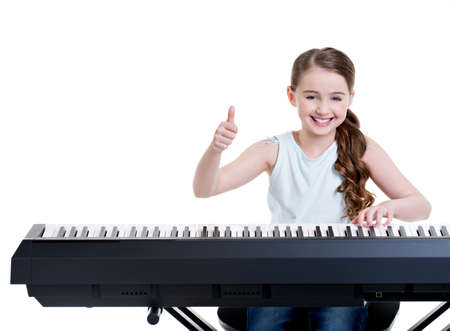 Cute happy smiling girl plays on the electric piano and shows thumbs up - isolated on white.